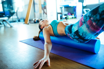 Young woman resting on pilates foam roller