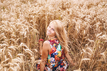 Cute blond girl sitting in a wheat field
