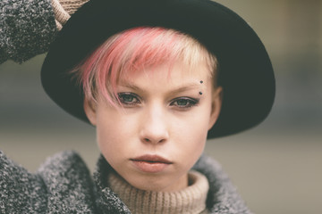 young woman with black hat and pink hair