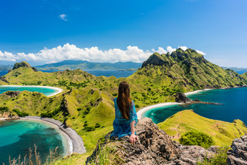 Rear view of a young woman enjoying the awesome view of Padar Island, while sitting on the top of a volcanic mountain during summer vacation in Indonesia Fototapete