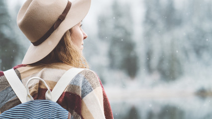 Attractive traveling woman spending time in front of incredible mountain lake. Wearing hat, poncho and backpack. Winter is coming, first snowfall. Wanderlust and boho style