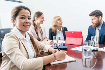 Portrait of a confident Asian business woman wearing formal outfits while sitting down during a decision-making meeting, in the conference room of a successful company
