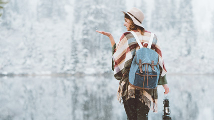 Handsome woman standing in front of amazing wild lake with kerosene lamp and catching first snow. Wearing hat, poncho and backpack. Winter is coming. Wanderlust and boho style