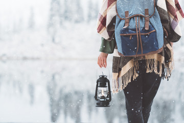 Woman standing in front of amazing lake view with kerosene lamp. Close-up. Wearing hat, poncho and backpack. Winter is coming, first snowfall. Wanderlust and boho style