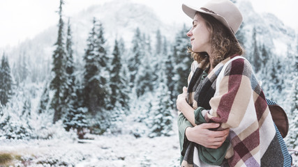 Handsome woman standing in the wild in front of amazing natural view. Wearing hat, poncho and backpack. Winter is coming, first snowfall. Wanderlust and boho style
