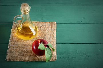 Red apples and apple cider vinegar on wooden table. Concept - healthy food from your garden. Top view.