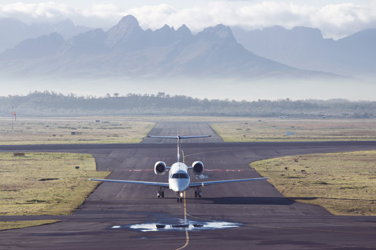 Aircraft taxiing at Cape Town airport with mountains in the background