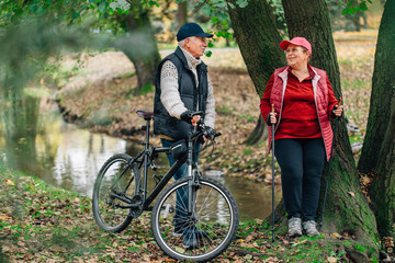 Pretty senior sport couple standing  in colorful autumn park near river. Mature woman with nordic walking poles and old man with bicycle resting outdoors.