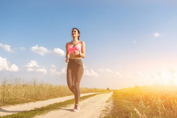 The woman running on the dirt road on the sunny background Wall mural