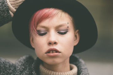 young woman with black hat and pink hair .