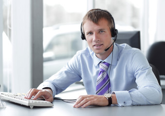Happy businessman in headphones smiling while looking at camera.