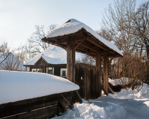 Sunny winter day at an old Romanian Homestead with a wooden handcrafted gate.