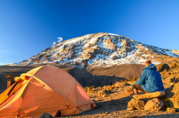 Evening view of Kibo with Uhuru Peak (5895m amsl, highest mountain in Africa) at Mount Kilimanjaro,Kilimanjaro National Park,seen from Karanga Camp at 3995m amsl. Tent and young hiker in foreground.