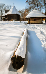 A small traditional wooden church and cottage covered in snow at the Village Museum, Bucharest, Romania