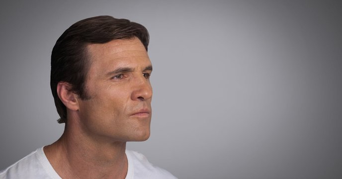 Man looking contemplatively with grey background