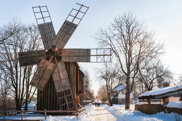 A traditional windmill on a snow-covered street at the open-air Village Museum in Bucharest, Romania.