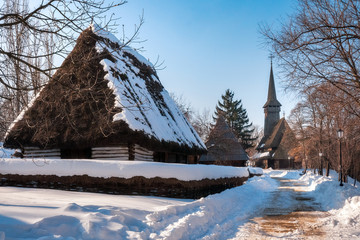 Pastoral landscape with traditional old cottage with a thatched roof covered in snow and a tall wooden church at the village museum in Bucharest, Romania.