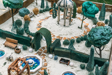 Miniature houses, toy landscape objects in sandbox. Anti-stress and soothing sand therapy.