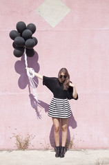 Beautiful woman holding black balloons