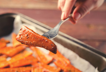 PIece of Roasted Caramelized organic Carrots with spices on fork in hand
