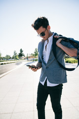 Young man with a bag using his phone in a street during a sunny day