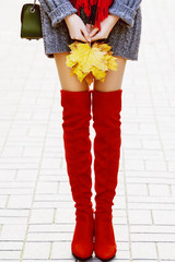 Fashionable woman wearing trendy red high, over the knee suede boots posing in street. Model holding yellow autumn leafs in her hands. Elegant city outfit. Female fashion concept