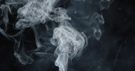 Puffs of white smoke over dark background