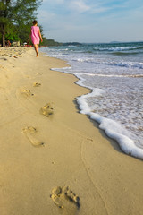 a young girl in a pink dress walks barefoot along the beach of Cambodia, along the seashore, leaving traces on the sand. the wave foams