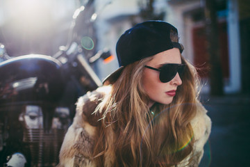 beautiful young stylish girl crouches by motorcycle