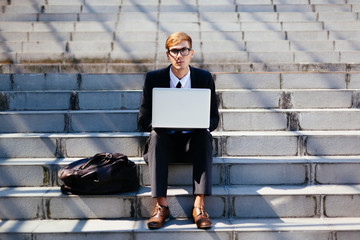 Smart Businessman Using Laptop for His Work Outdoor Sitting on the Stairs