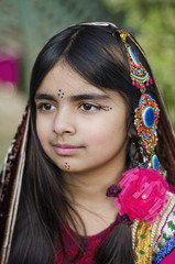 AN adolescent girl in ornate traditional dress