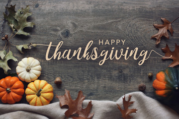 Happy Thanksgiving script with pumpkins and leaves over dark wooden background