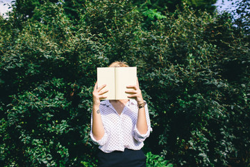 Woman holding a book in front of face