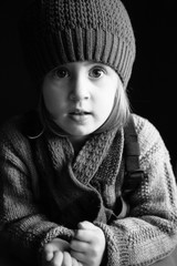 a girl in a winter hat looks pensively into the camera