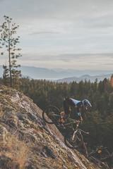 Men mountain biking through the forest in british columbia