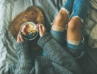 Healthy winter breakfast in bed. Woman in grey sweater and jeans eating rice coconut porridge with figs, berries, hazelnuts, top view. Clean eating, diet, vegetarian, vegan, comfort food concept