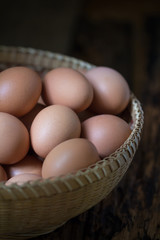 Close up of eggs in a basket on wooden table background