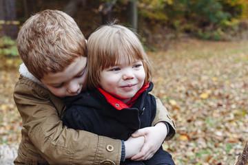 A little boy hugs his sister.
