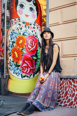 Hippie woman sitting near matryoshka