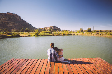 Couple sitting at the edge of a pier overlooking a dam