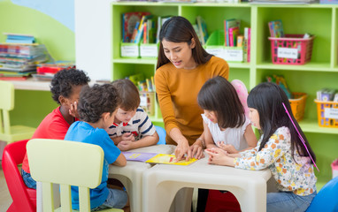 Asian female teacher teaching mixed race kids reading book in classroom,Kindergarten pre school concept.