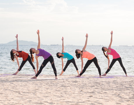 Yoga class at sea beach in evening ,Group of people doing Triangle poses with clam relax emotion at beach,Meditation pose,Wellness and Healthy balance lifestyle.