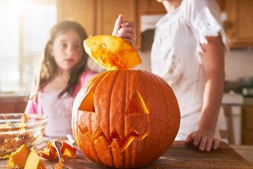 fun activity - mother and daughter having fun carving pumpkin into jack o lantern for halloween