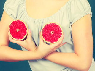 Woman holding red grapefruit on breast