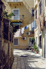 Side street in Corfu old town with laundry hanging between buildings