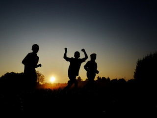 Silhouettes of boys running