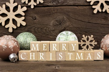 Merry Christmas wooden blocks with decor over a rustic wood background