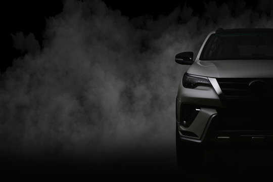 Studio shot of white car isolated on black background with shadow and smoke fog.