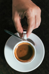 Drinks: hand and cup of coffee espresso
