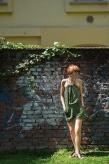 Fashionable Ginger Woman in Front of a Brick Wall